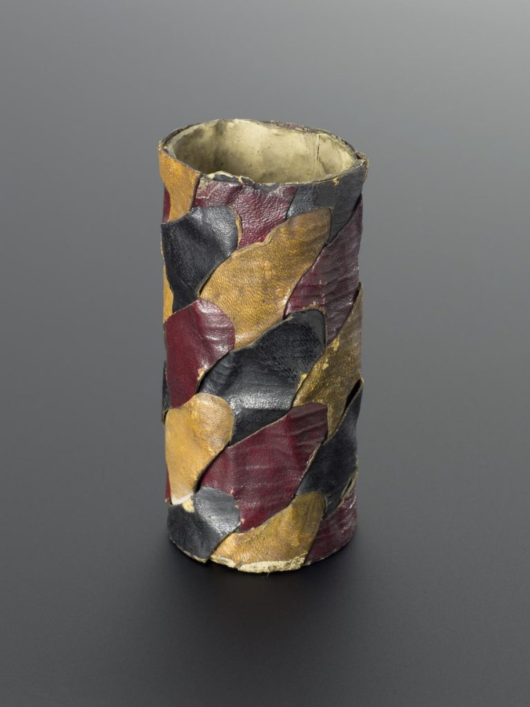 Locked cylinder of three interlacing sheets in red, yellow and black leather, elliptical perforations, by Alexander Crum Brown, c.1914. Science Museum Group Collection © The Board of Trustees of the Science Museum