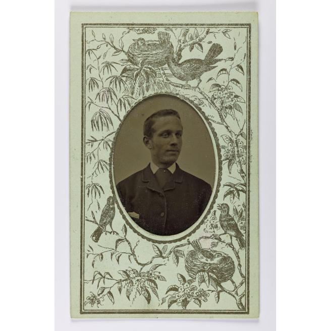 Gem-size tinted tintype, depicting a man, mounted in a Christmas greetings decorated carte-de-visite card, by an unknown photographer, 1880s - 1890s