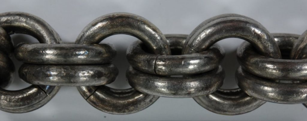 Closer inspection of the tarnished chains before cleaning.