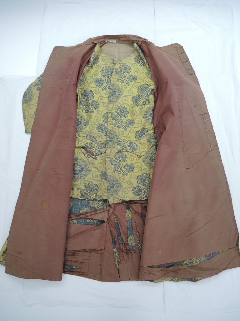 Banyan laid out showing the internal waistcoat before conservation.