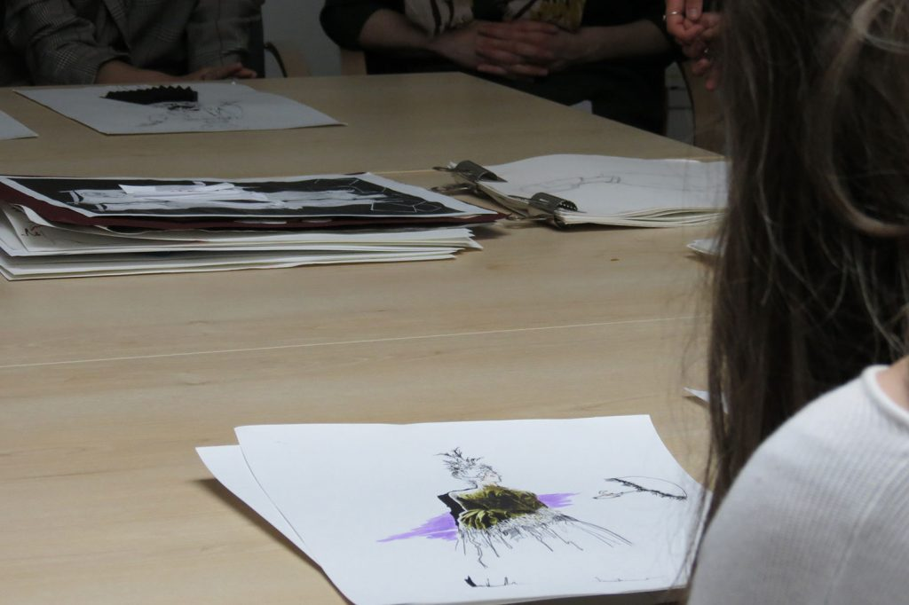 A fashion student presents her work to the panel