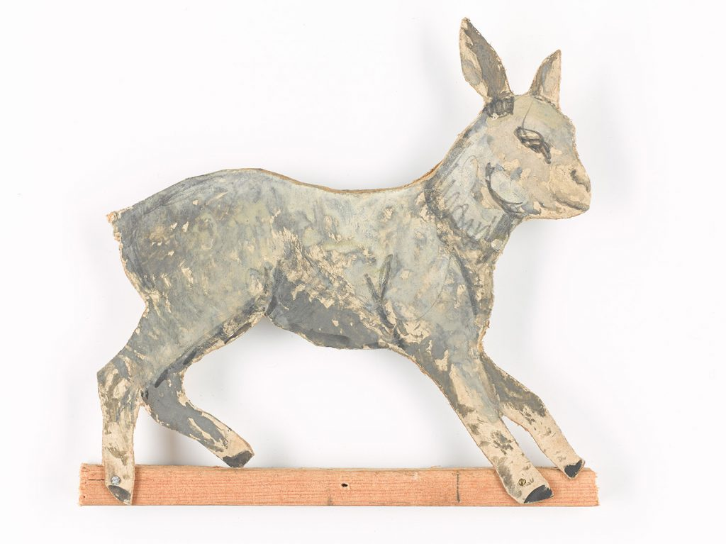 A lamb, a tradition emblem from Nativity scenes, at once representing Christ (the lamb of God) and as one of the flock belonging to the shepherds.