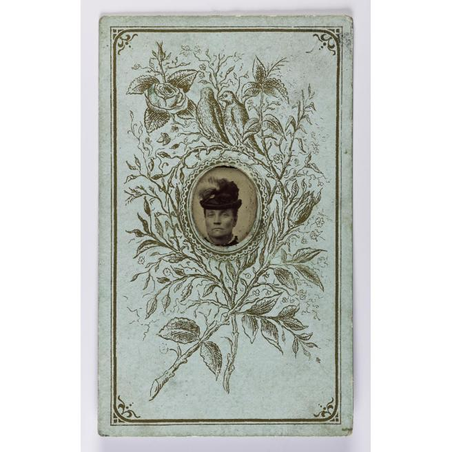 Gem-size tintype, depicting a woman wearing a hat, mounted in a Christmas greetings decorated carte-de-visite card, by J. Jewell of Liverpool, Manchester, Glasgow and Newcastle-upon-Tyne, 1880s - 1890s