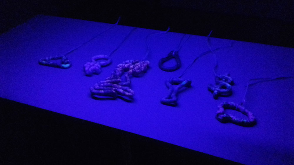 Mallory Weston's latest body of work on display in Platina. Made from carved stone that has natural fluorescent minerals, her pendants appear normal under natural light, but under UV light they glow with neon.