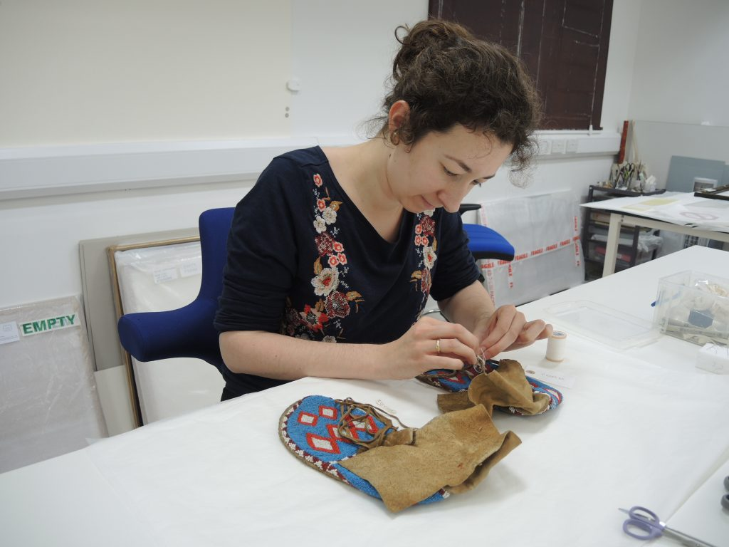 Attaching a museum accession numbers onto a pair of shoes made with animal skin decorated with glass beads.