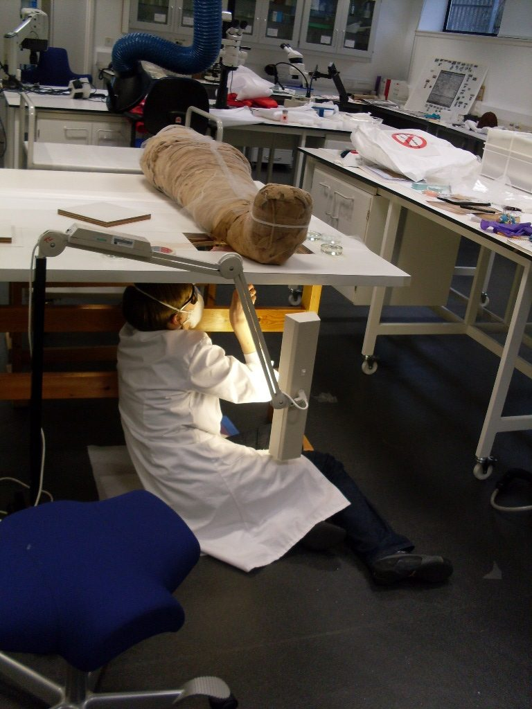 Work carried out on the underside of a, Egyptian mummy using a sewing table.