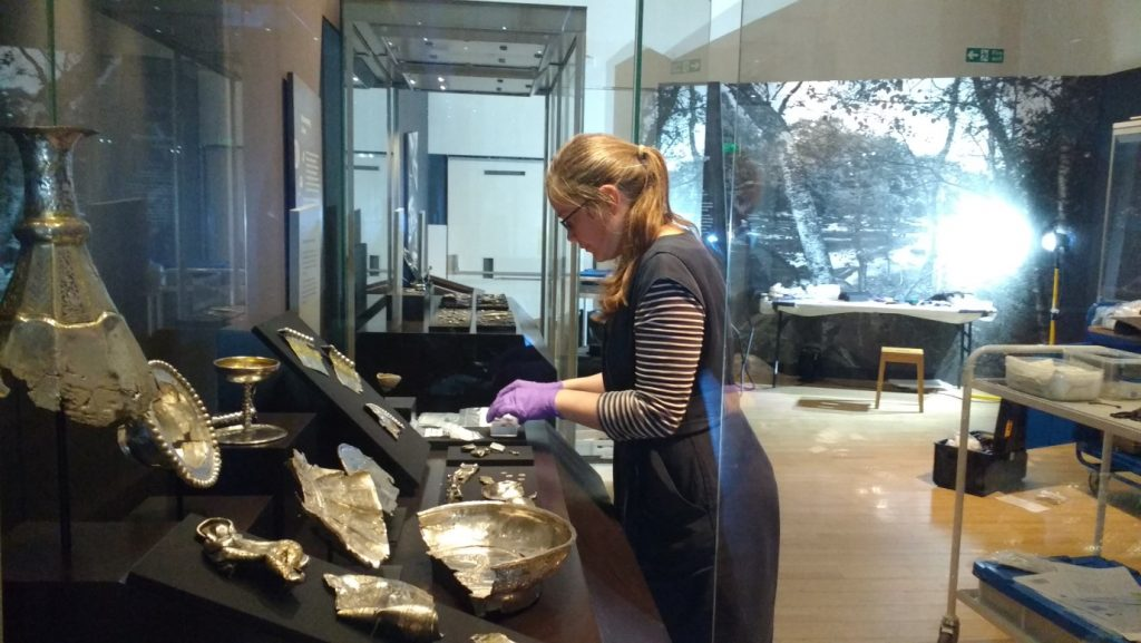 Alice sorting out the final positioning of the objects inside the display cases.