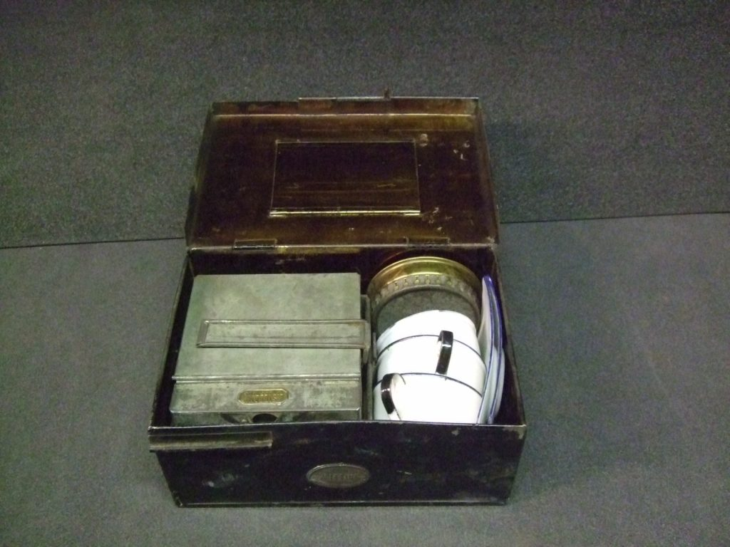 The tin tea set packed up in its case.