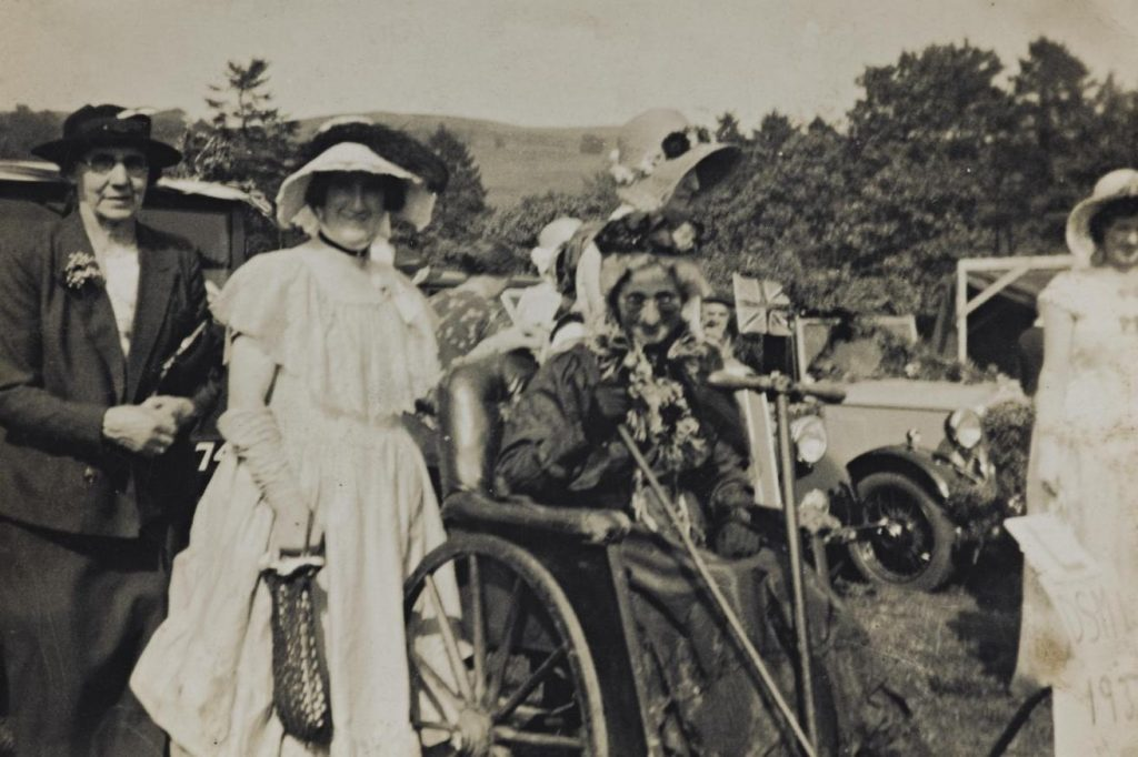 Digital copy of black and white photograph of a fancy dress party, including Mary Davidson (second from left) and Thomsina Davidson (in wheelchair), at Moniaive Gala, Dumfriesshire in the 1920s. From the Scottish Life Archive, SLA.DIG.9.22.