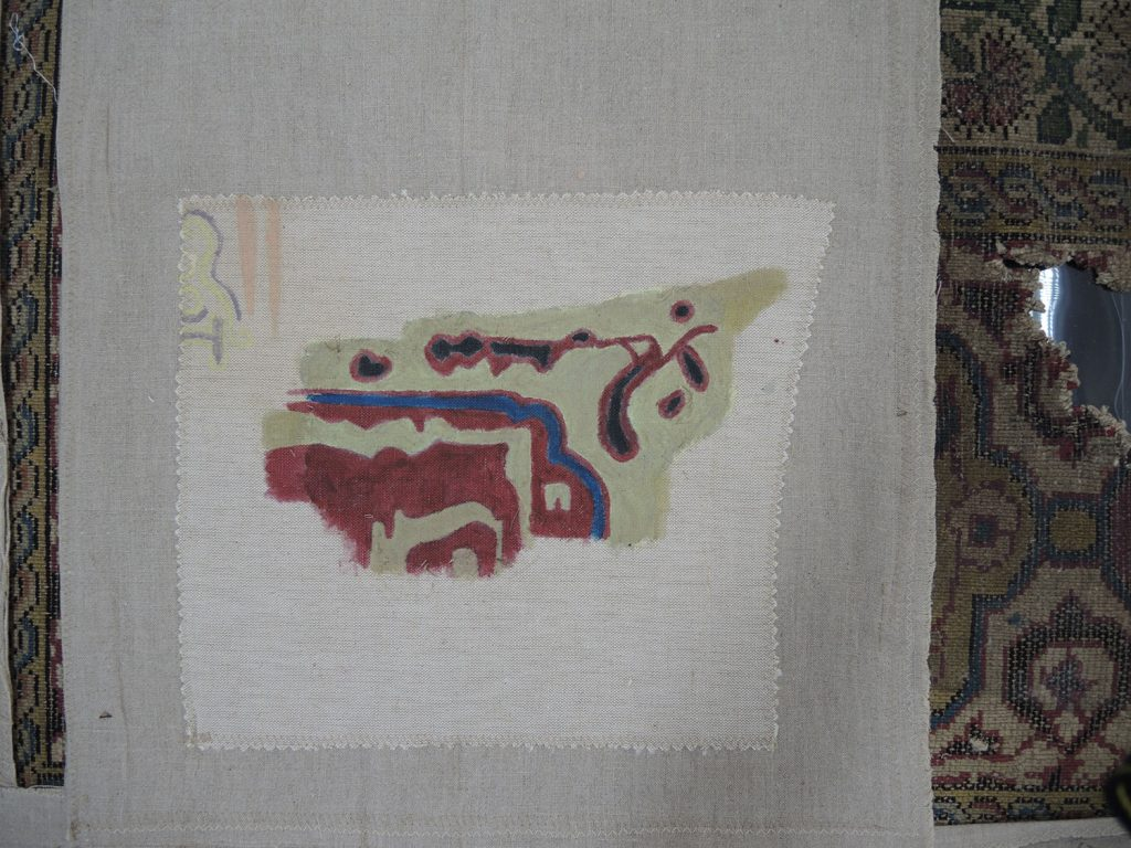 The old hand-painted patch after removal from the reverse of the carpet