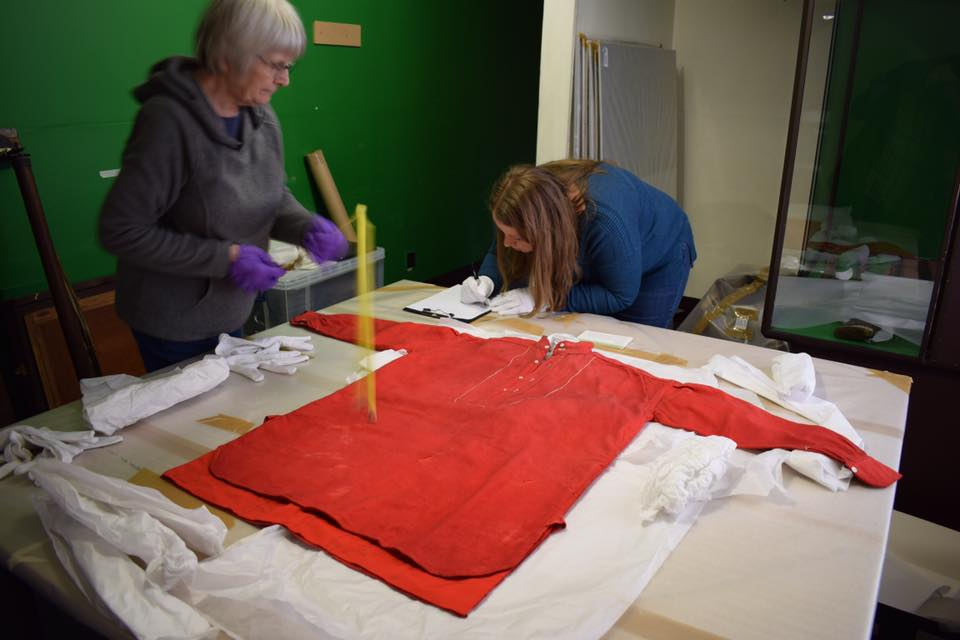 Volunteers checking Dr Livingstone's iconic Turkey Red shirt for any pest damage