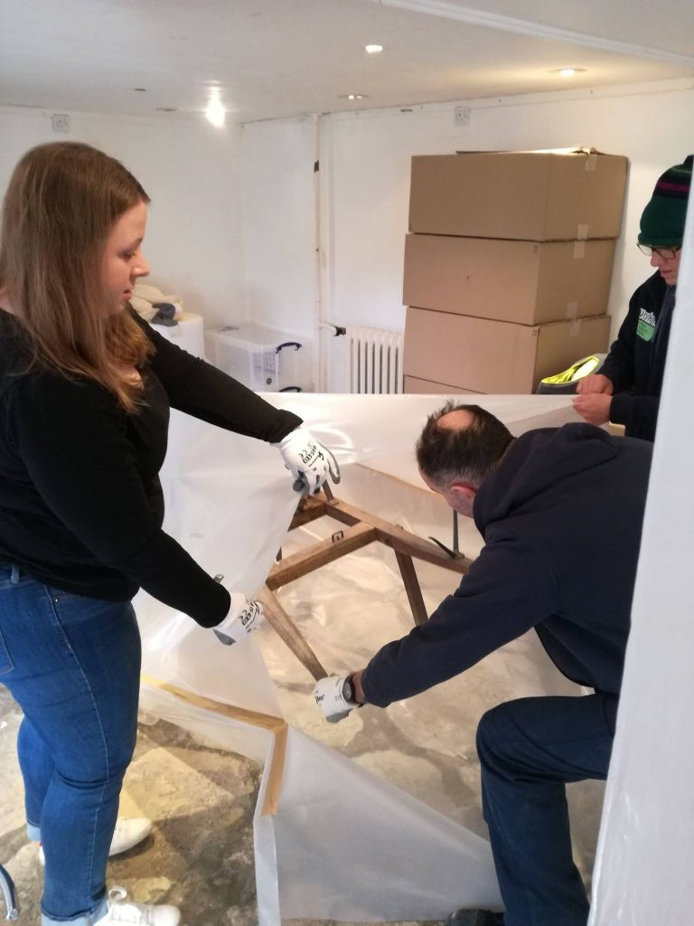 Volunteers and art handlers packing an agricultural tool infested with woodworm