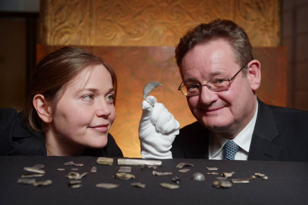 Alice Blackwell, Curator of Medieval Archaeology and History, and Hamish Torrie, Director of Corporate Social Responsibility at The Glenmorangie Company, looking at re-discovered silver from the Gaulcross hoard.