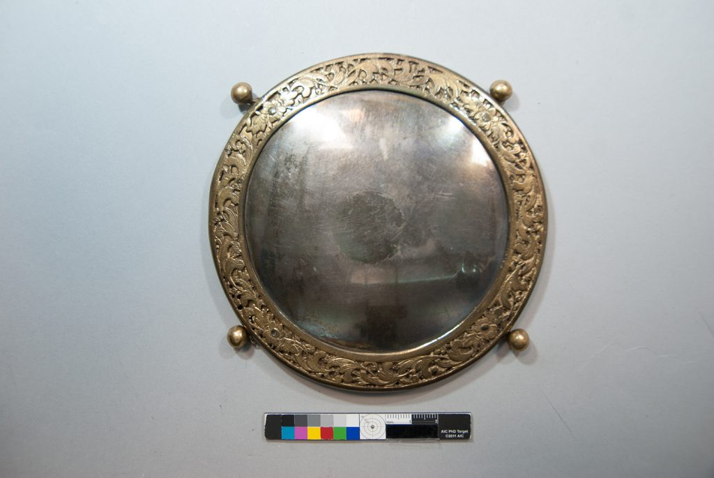 One of the silvered metal medallions before conservation.