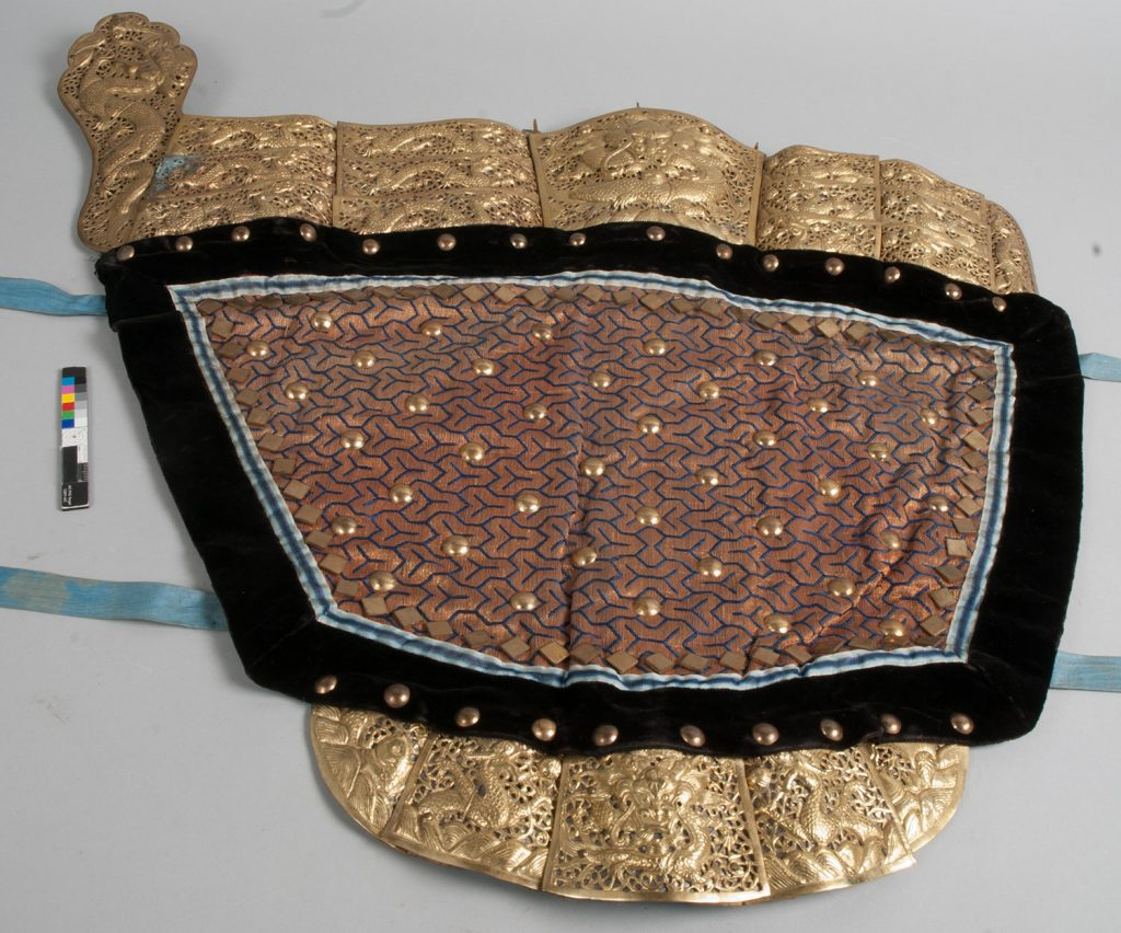 The right shoulder attachment of the armour, with gold brocade, blue silk, black velvet, copper-alloy studs and gilt decorative attachments, before conservation.]