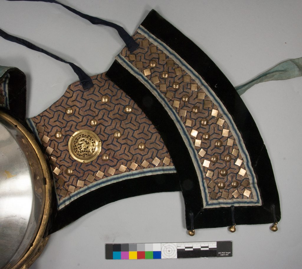 The brass studs and gilt attachments on the brocade neck curtain. These were cleaned with solvents, and so the brocade had to be protected whilst cleaning was in progress.