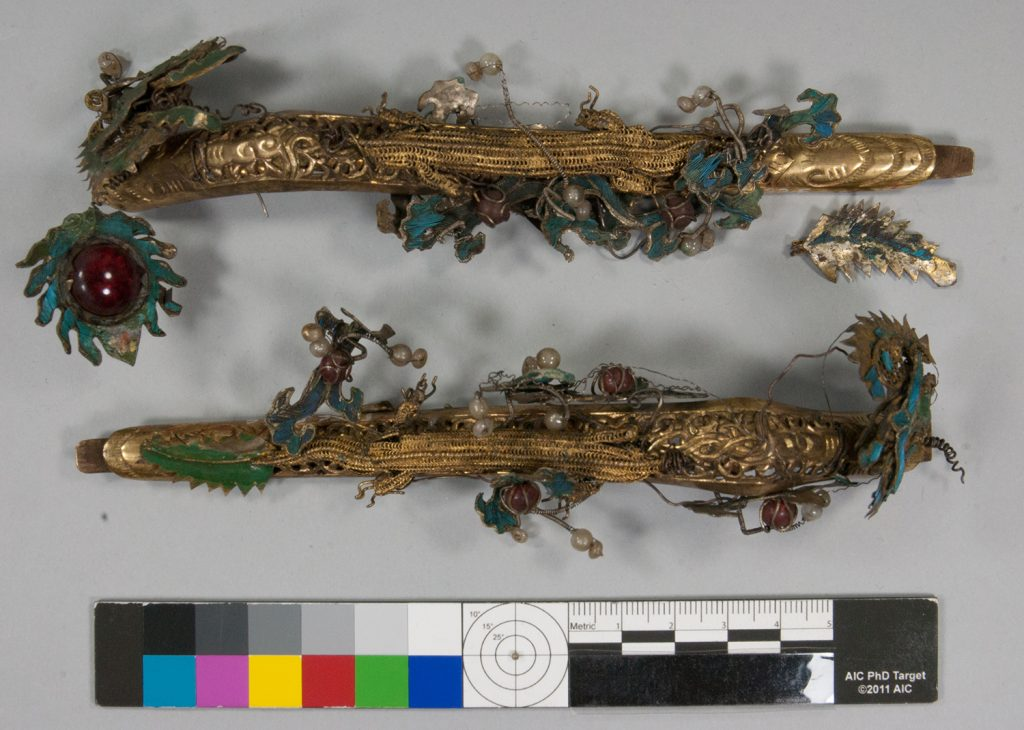 Two detachable ornaments for the helmet in the shape of dragons before conservation. Of gilt copper-alloy with leaf and scroll ornaments with wire, glass and paste beads, and tian-tsui decoration.
