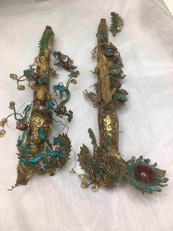 The two dragon attachments with tian-tsui decoration: on the left post-cleaning, on the right before cleaning.