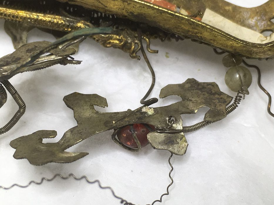 An accretion on the underside of one of the gilt decorations on the dragon attachment.