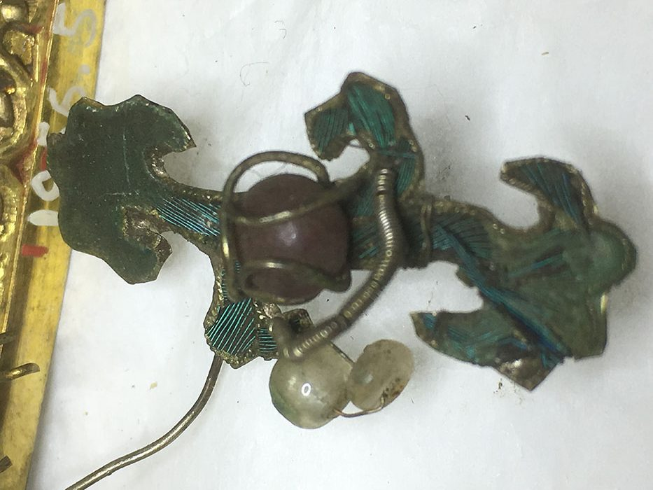 Hidden blue: one of the gilt decorations of the dragon attachment before conservation showing the kingfisher feathers and green paste.