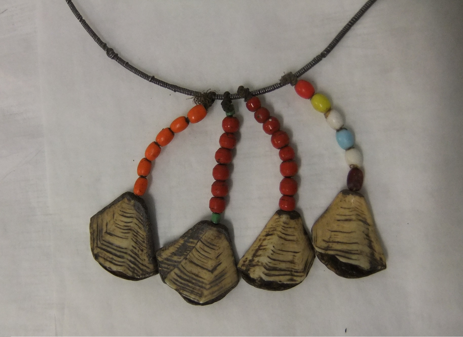 Detail of girl's necklace made from wire with four pendants of coloured beads terminating in pieces of tortoise shell