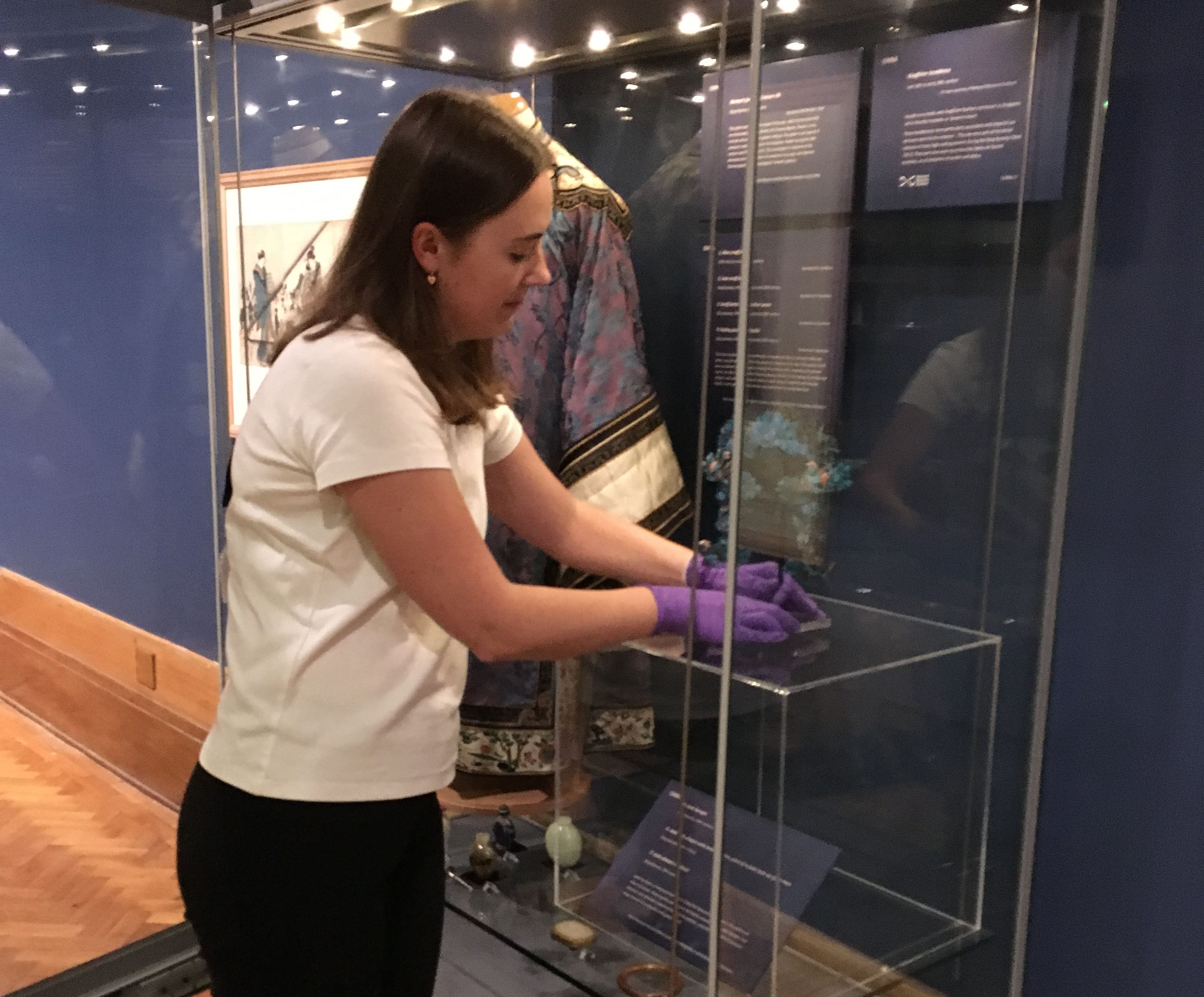 Installing the kingfisher hair piece in the showcase at Perth Museum and Art Gallery.
