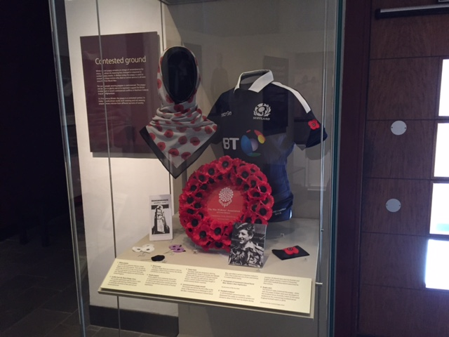 Display case with poppy-related objects