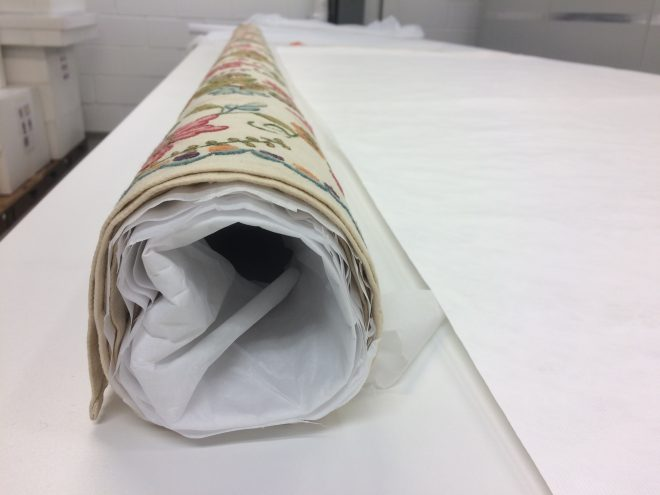 Step 5. The textile is then rolled slowly around the tube with the creases being smoothed out and edges realigned.