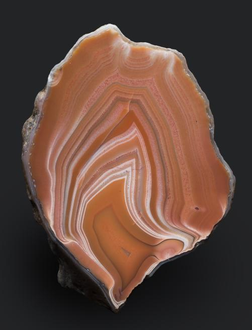 "Quartz, variety agate - many layered reddish-brown and pale grey ""flame"" banded with some common quartz infill - polished on one face - Agate book, F.61, p.28 - from Scurdie Ness, Montrose, Angus"