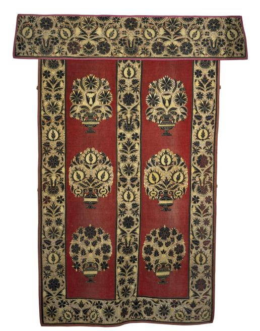 Red wool with napped surface; applique of black velvet pile, embroidered with gold and blue silk braid and yellow and blue silk thread