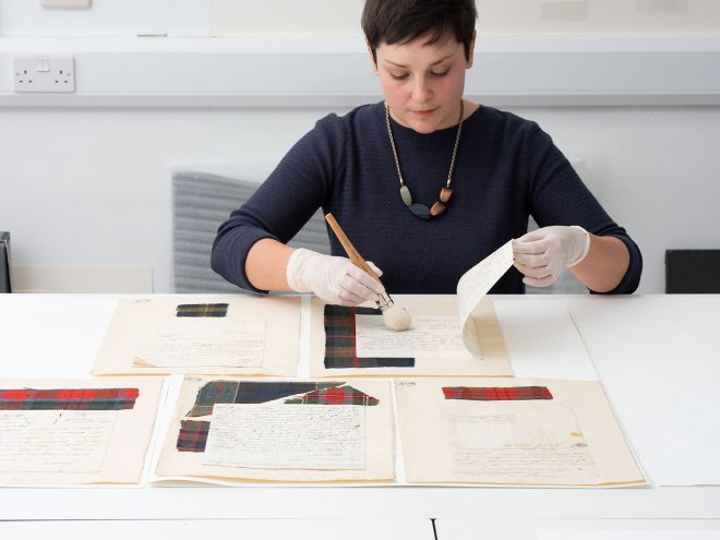 Paper conservator Emma Davey with letters of a tartan weaving company featuring swatches of fabric