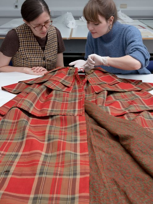 Research fellow Rosanne Waine and textile conservator Rosie Nuttall examine a stylish tartan cloak, a new acquisition that will feature in the exhibition
