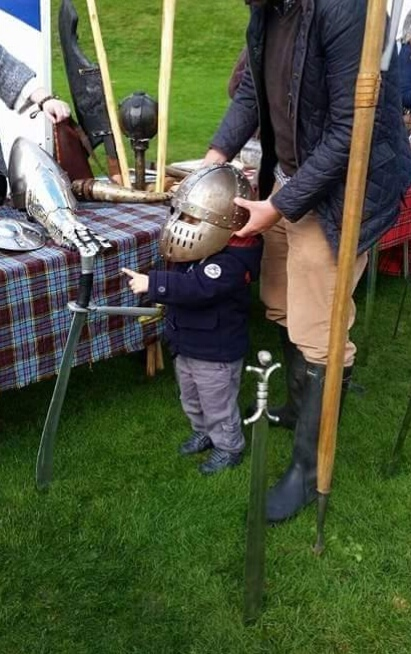 Julie's son Michael at a medieval re-enactment event wearing a reproduction helmet