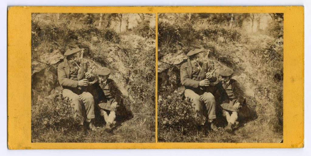 Stereocard entitled 'The Lesson on the Bagpipes (Braemar)', depicting a man playing the bagpipes and teaching a boy in a kilt, by an unknown photographer, 1870s.