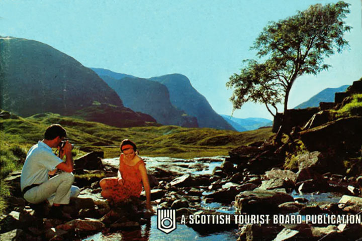'Holidays in Scotland' Scottish Tourist Board campaign from 1969. showing a man and woman seated by a river, with mountains in the background.