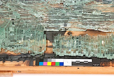 Glass and wood sculpture entitled Wall Piece, with a broken section of glass at the bottom