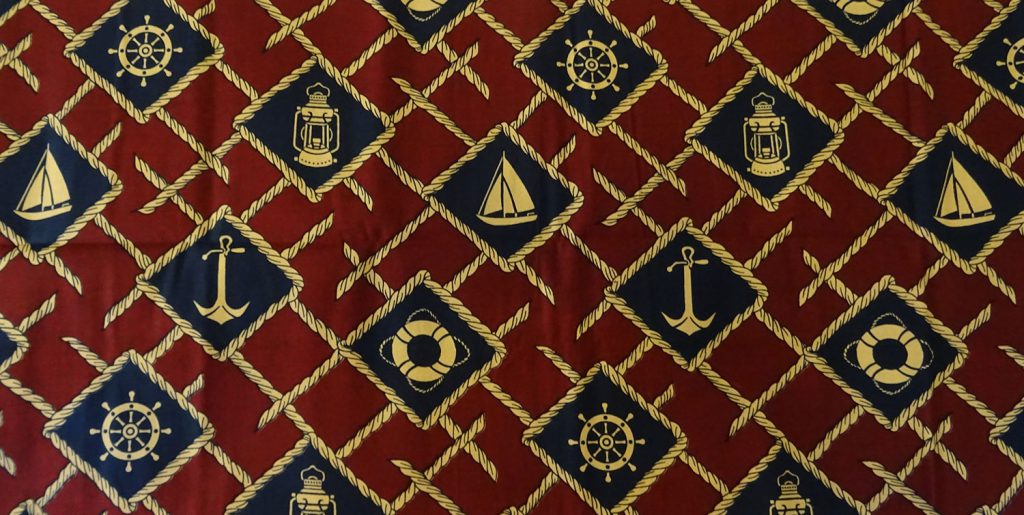 Brownand yellow capulana cloth with a pattern of boats, anchors, ships' wheels and life belts
