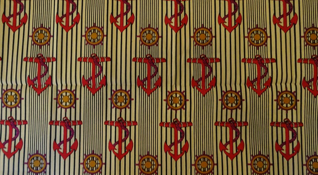 Striped yellow and black capulana cloth decorated with red anchors and ships' wheels