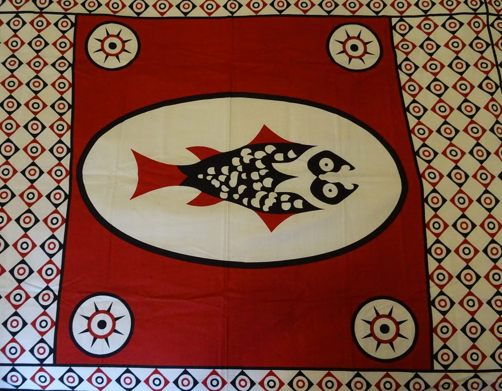 Red capulana cloth with a blue and white border and large blue and white fish in the middle