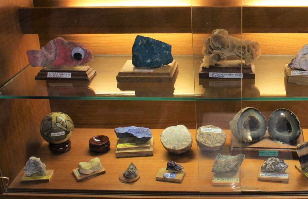 Geology display at the Stonehaven Tolbooth Museum, showing a range of minerals and including one pink fish-shaped mineral with a google eye attached!