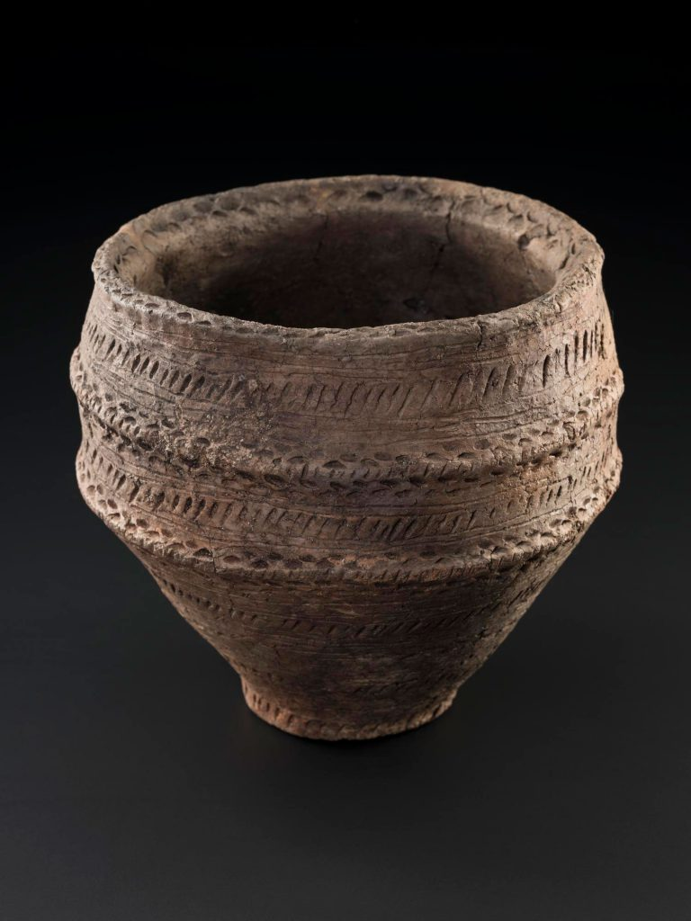 A food vessel from Machrie Moor - a brown pot decorated with score marks and dots.