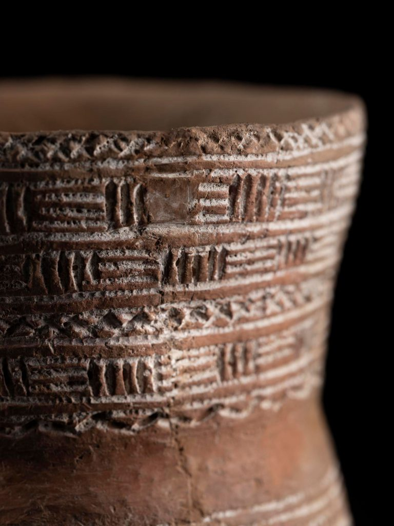 Close up of decoration on a Bronze Age Beaker, showing a geometric pattern of horizontal, vertical and diagonal lines.