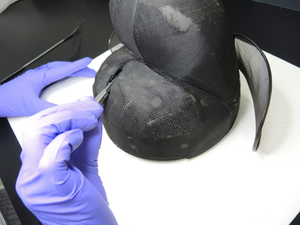 The conservator is inserting a thread splint using tweezers.