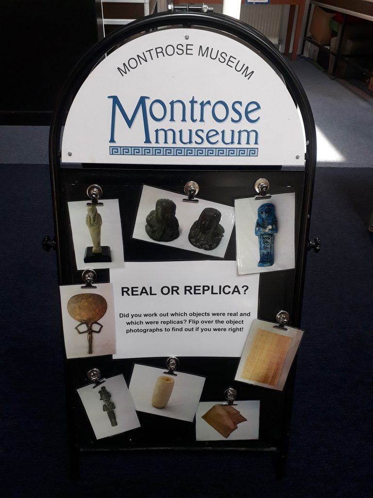 Real or Replica display at Montrose Museum, with images of ancient Egyptian artefacts pinned to a board.