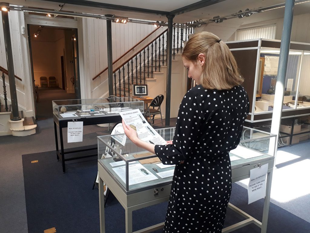 A visitor using their detective skills to deduce which objects are from ancient Egypt or modern fakes in Real or Replica.