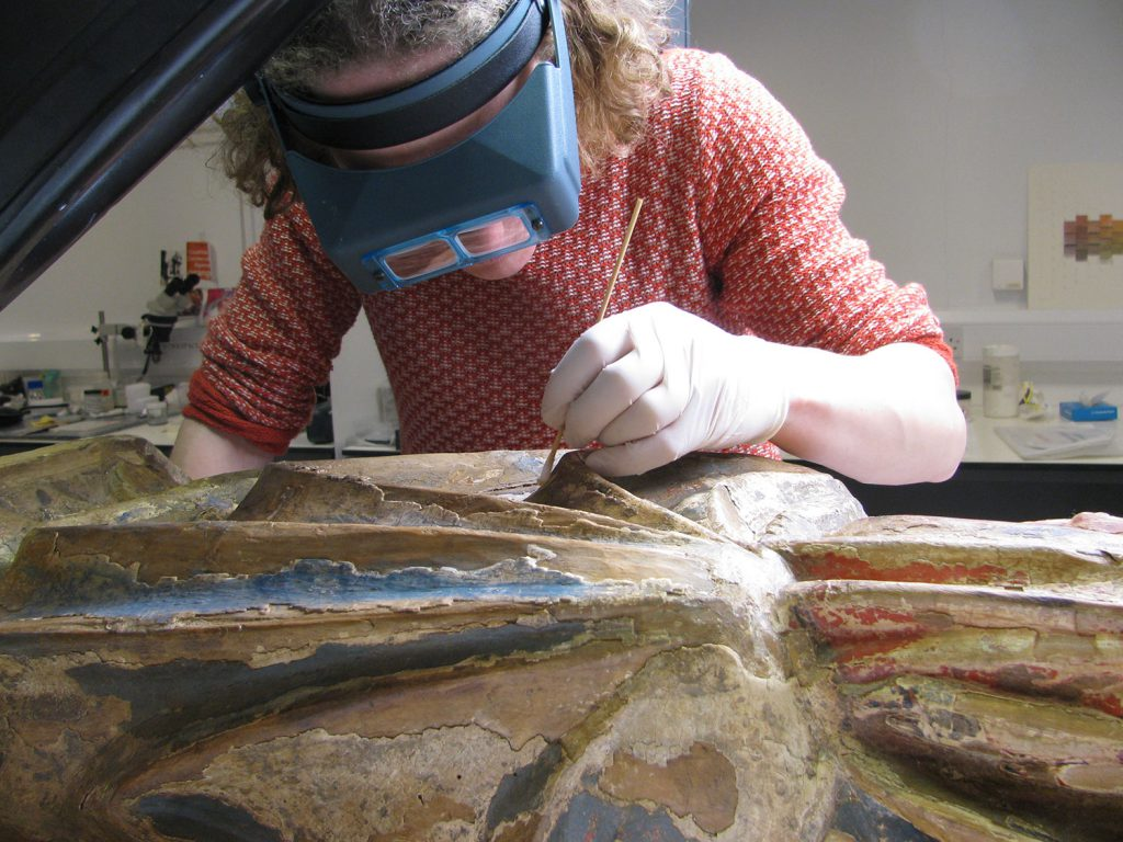 Conservator Diana inspecting the surface of the Madonna using an Optivisor.