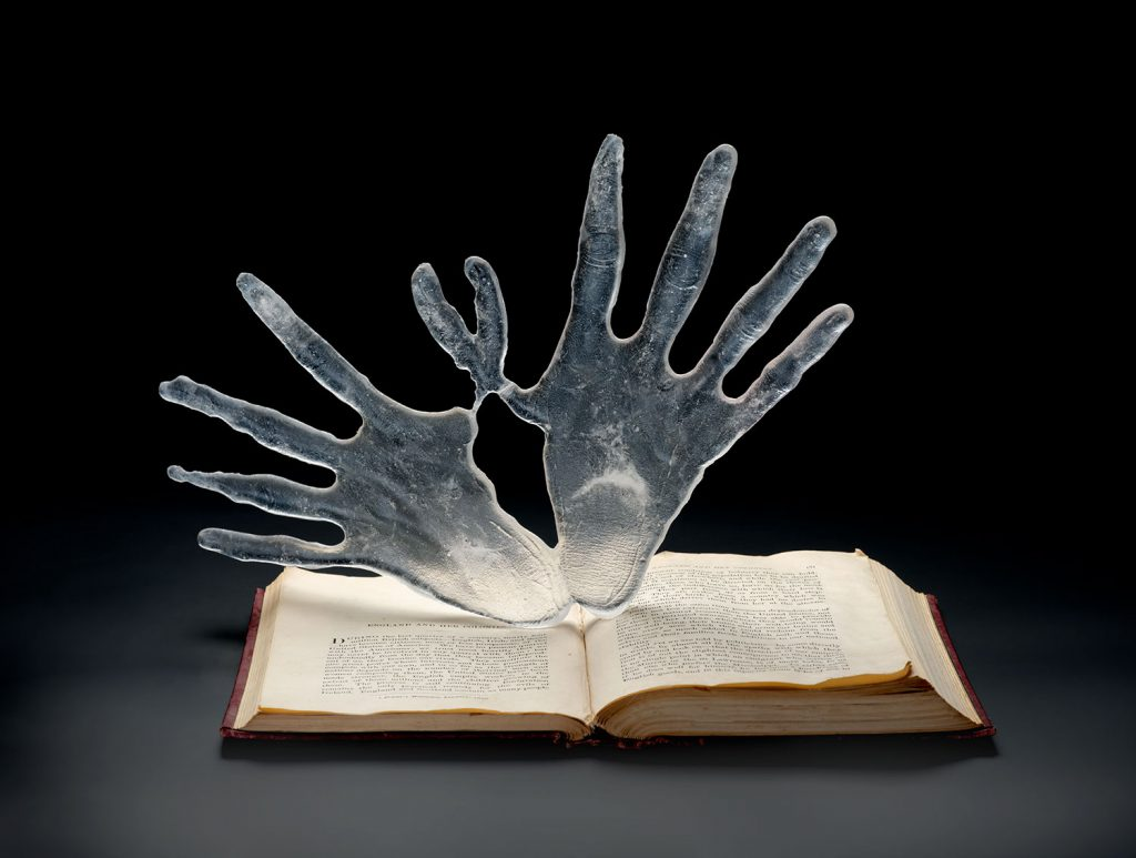The final piece, with the glass hands standing upright in the open book