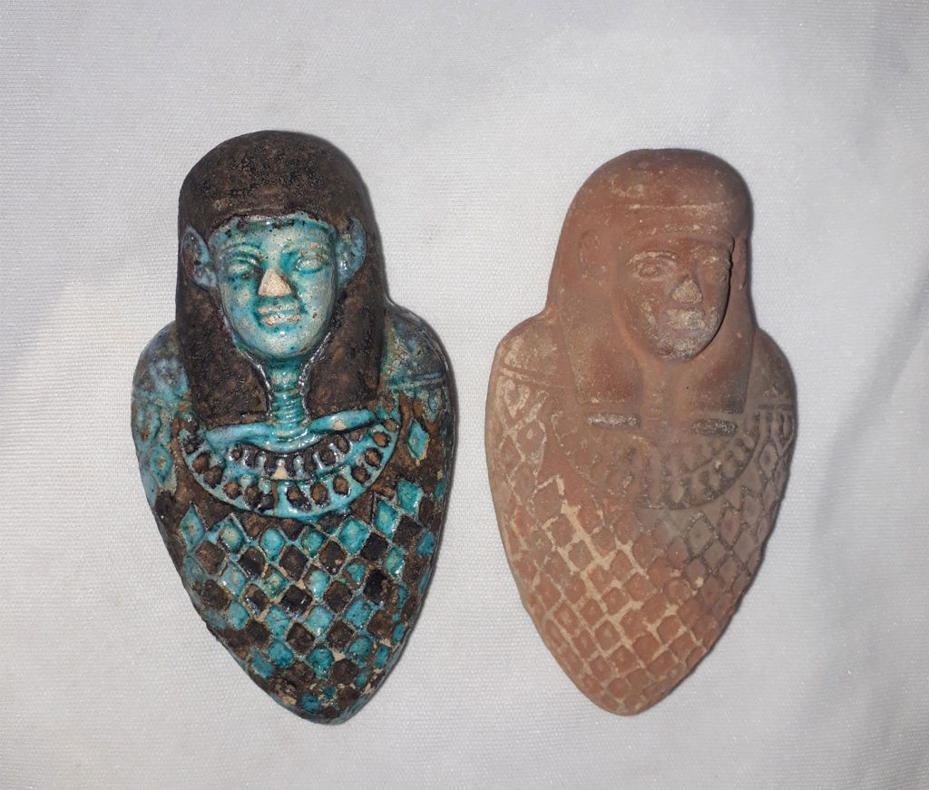 Two heart-shaped amulets, one coloured blue the other plain