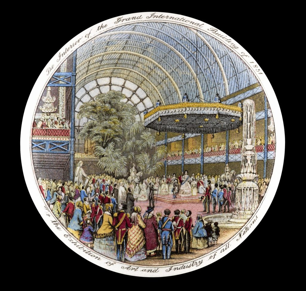 A circular image showing hoards of visitors admiring exhibitions in The Crystal Palace at The Great Exhibition. The crowd seem to be watching a performance on a bandstand-like structure. The huge room is lush with leafy plants, and a tall fountain is flowing.