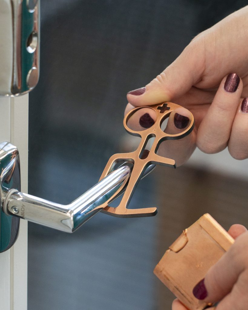 A copper metal tool that resembles a key and pair of scissors combination being used to open door handle.